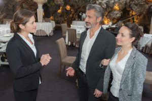 restaurant manager welcomes a couple in the restaurant